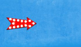 Segno metallico illuminato variopinto d'annata a forma di freccia rosso dell'esposizione con le lampadine d'ardore sul lato sinis Fotografie Stock Libere da Diritti