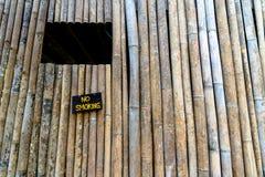 Segno non fumatori allegato alla vecchia parete di bambù immagine stock
