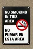 Segno non fumatori bilingue Immagine Stock