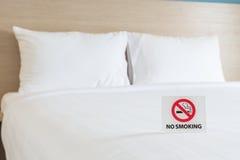 Segno NON FUMATORI sul letto nella camera di albergo Fotografia Stock
