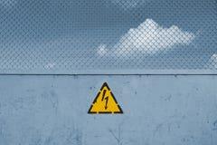 Segno pericoloso, alta tensione e griglia Immagine Stock