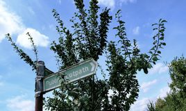 Segno pubblico arrugginito del sentiero per pedoni visto vicino ad una siepe di arbusti in un campo britannico fotografia stock
