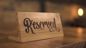 Segno riservato della tavola per il sedile di prenotazione in ristorante elegante per la cena della candela Etichetta riservata d archivi video