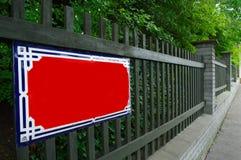 Segno rosso in bianco vuoto di nome della via sul recinto verde fotografie stock