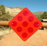 Segno rosso d'avvertimento del riflettore che appende sulla barriera di modo di didascalia Fotografia Stock