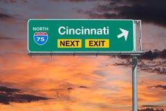 Segno seguente dell'uscita dell'autostrada senza pedaggio dell'itinerario 75 di Cincinnati con il cielo di tramonto Fotografie Stock