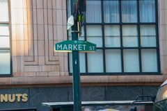 Segno verde di Market Street su un palo verde con una grande finestra della multi-lastra di vetro su un vecchio edificio per uffi fotografia stock libera da diritti