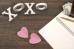 Segno XOXO, due cuori, penna, carta, soldi su fondo di legno Fotografia Stock