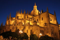 Segovia Cathedral, Spain. A picture of Segovia Cathedral in Segovia Spain in the evening with a view of towers, the façade of the building, lights and trees stock photo