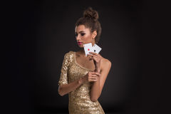Segra för kvinna - den unga kvinnan i en flott guld- klänning som rymmer två överdängare, en poker av överdängare, card kombinati arkivfoto