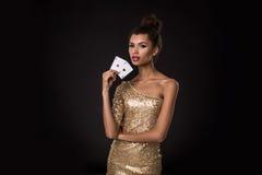 Segra för kvinna - den unga kvinnan i en flott guld- klänning som rymmer två överdängare, en poker av överdängare, card kombinati arkivbild