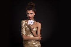 Segra för kvinna - den unga kvinnan i en flott guld- klänning som rymmer två överdängare, en poker av överdängare, card kombinati royaltyfri bild