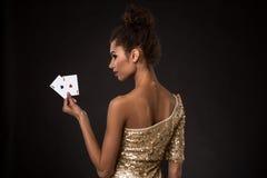 Segra för kvinna - den unga kvinnan i en flott guld- klänning som rymmer två överdängare, en poker av överdängare, card kombinati royaltyfria bilder