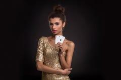 Segra för kvinna - den unga kvinnan i en flott guld- klänning som rymmer två överdängare, en poker av överdängare, card kombinati royaltyfri fotografi