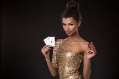 Segra för kvinna - den unga kvinnan i en flott guld- klänning som rymmer två överdängare och två röda chiper, en poker av överdän royaltyfri bild