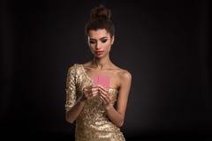 Segra för kvinna - den unga kvinnan i en flott guld- klänning som rymmer två kort, en poker av överdängare, card kombination sinn fotografering för bildbyråer