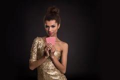 Segra för kvinna - den unga kvinnan i en flott guld- klänning som rymmer två kort, en poker av överdängare, card kombination sinn arkivbilder