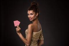 Segra för kvinna - den unga kvinnan i en flott guld- klänning som rymmer två kort, en poker av överdängare, card kombination fotografering för bildbyråer