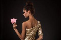Segra för kvinna - den unga kvinnan i en flott guld- klänning som rymmer två kort, en poker av överdängare, card kombination royaltyfria foton