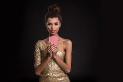 Segra för kvinna - den unga kvinnan i en flott guld- klänning som rymmer två kort, en poker av överdängare, card kombination sinn royaltyfri bild