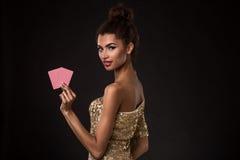Segra för kvinna - den unga kvinnan i en flott guld- klänning som rymmer två kort, en poker av överdängare, card kombination royaltyfria bilder