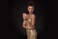 Segra för kvinna - den unga kvinnan i en flott guld- klänning som rymmer två kort, en poker av överdängare, card kombination sinn royaltyfria bilder