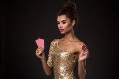 Segra för kvinna - den unga kvinnan i en flott guld- klänning som rymmer två kort och två röda chiper, en poker av överdängare, c arkivfoton