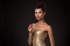 Segra för kvinna - den unga kvinnan i en flott guld- klänning som rymmer två röda chiper, en poker av överdängare, card kombinati arkivfoton