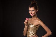 Segra för kvinna - den unga kvinnan i en flott guld- klänning som rymmer två röda chiper, en poker av överdängare, card kombinati royaltyfri foto