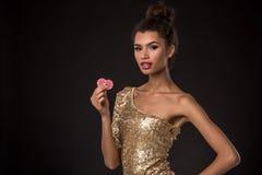 Segra för kvinna - den unga kvinnan i en flott guld- klänning som rymmer två röda chiper, en poker av överdängare, card kombinati arkivbilder