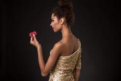 Segra för kvinna - den unga kvinnan i en flott guld- klänning som rymmer två röda chiper, en poker av överdängare, card kombinati royaltyfria foton