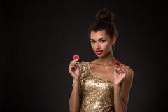 Segra för kvinna - den unga kvinnan i en flott guld- klänning som rymmer två röda chiper, en poker av överdängare, card kombinati arkivfoto