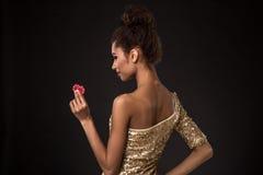 Segra för kvinna - den unga kvinnan i en flott guld- klänning som rymmer två röda chiper, en poker av överdängare, card kombinati royaltyfri fotografi