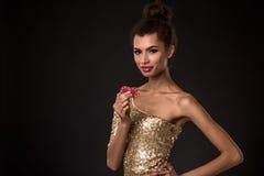 Segra för kvinna - den unga kvinnan i en flott guld- klänning som rymmer två röda chiper, en poker av överdängare, card kombinati royaltyfri bild