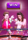 Segra knappen med två kvinnor som spelar i kasino royaltyfria bilder
