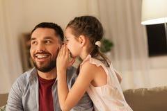 Segredo de sussurro da filha feliz a genar em casa fotografia de stock