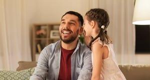 Segredo de sussurro da filha feliz a genar em casa imagem de stock royalty free