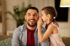 Segredo de sussurro da filha feliz a genar em casa fotos de stock royalty free