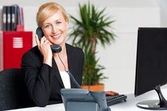 Segretaria che comunica sul telefono con il cliente fotografie stock libere da diritti