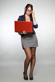 Segretaria con il computer portatile rosso immagine stock