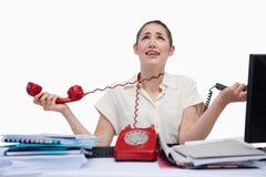 Segretaria sollecitata che risponde ai telefoni Fotografia Stock