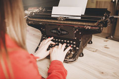 Segretario alla vecchia macchina da scrivere con il telefono Usando della giovane donna ty Fotografie Stock Libere da Diritti