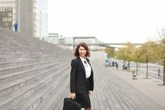 Segretario caucasico femminile che sta sulle scale con la borsa e sulle alte costruzioni nel fondo Fotografie Stock Libere da Diritti