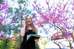 Segretario femminile allegro in vetri che parla dallo smartphone in parco di fioritura con i documenti Immagini Stock Libere da Diritti