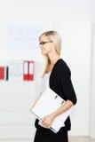 Segretario femminile che cammina attraverso l'ufficio Fotografie Stock