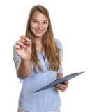 Segretario femminile che indica alla macchina fotografica con la penna Fotografia Stock