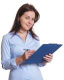 Segretario femminile con le note di scrittura dei capelli scuri su una lavagna per appunti Immagini Stock Libere da Diritti