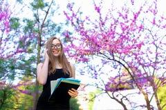 Segretario femminile piacevole in vetri che parla dallo smartphone in parco di fioritura con i documenti Fotografia Stock