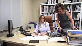 Segretario infelice con il mucchio di lavoro nell'ufficio archivi video