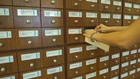Segretario sorridente che cerca gli archivi nei cassetti del casellario archivi video